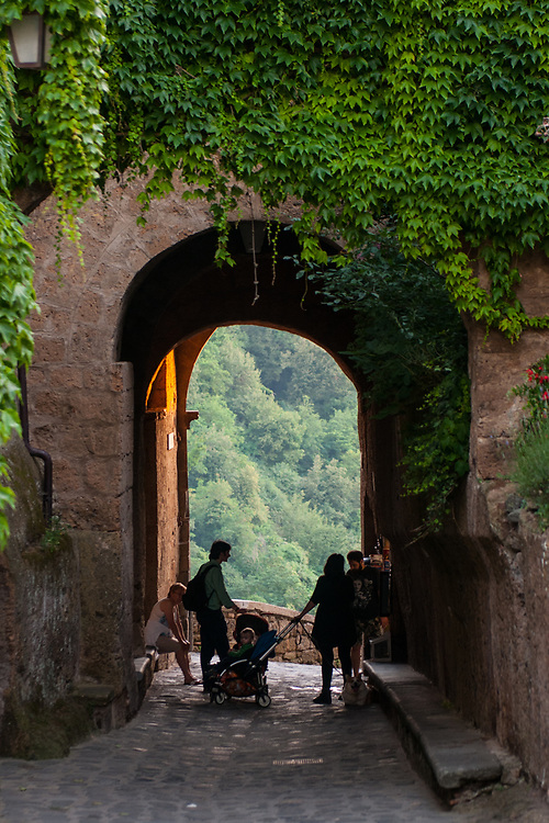 Citizen rest under a portico in the village of Civita di Bagnoregio.<br /> Civita di Bagnoregio is a town in the Province of Viterbo in central Italy, a suburb of the comune of Bagnoregio, 1 kilometre (0.6 mi) east from it. It is about 120 kilometres (75 mi) north of Rome. Civita was founded by Etruscans more than 2,500 years ago. Bagnoregio continues as a small but prosperous town, while Civita became known in Italian as La citt&agrave; che muore (&quot;The Dying Town&quot;). Civita has only recently been experiencing a tourist revival. The population today varies from about 7 people in winter to more than 100 in summer.The town was placed on the World Monuments Fund's 2006 Watch List of the 100 Most Endangered Sites, because of threats it faces from erosion and unregulated tourism.