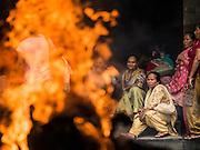 05 AUGUST 2015 - KATHMANDU, NEPAL: Nepalese Buddhist women watch a body burn at a cremation in Kathmandu.    PHOTO BY JACK KURTZ