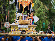 16 JULY 2016 - UBUD, BALI, INDONESIA: Children ride on a sarcophagus to the cremation site in Ubud. Local people in Ubud exhumed the remains of family members and burned their remains in a mass cremation ceremony Wednesday. Almost 100 people were cremated and laid to rest in the largest mass cremation in Bali in years this week. Most of the people on Bali are Hindus. Traditional cremations in Bali are very expensive, so communities usually hold one mass cremation approximately every five years. The cremation in Ubud concluded Saturday, with a large community ceremony.     PHOTO BY JACK KURTZ