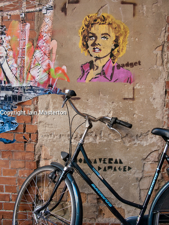 Bicycle parked beside wall with artistic graffiti in alleyway in Prenzlauer Berg Berlin