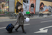 A man carrying a lighting fixture attached to his hand, crosses the road, on 22nd November 2017, in London England.