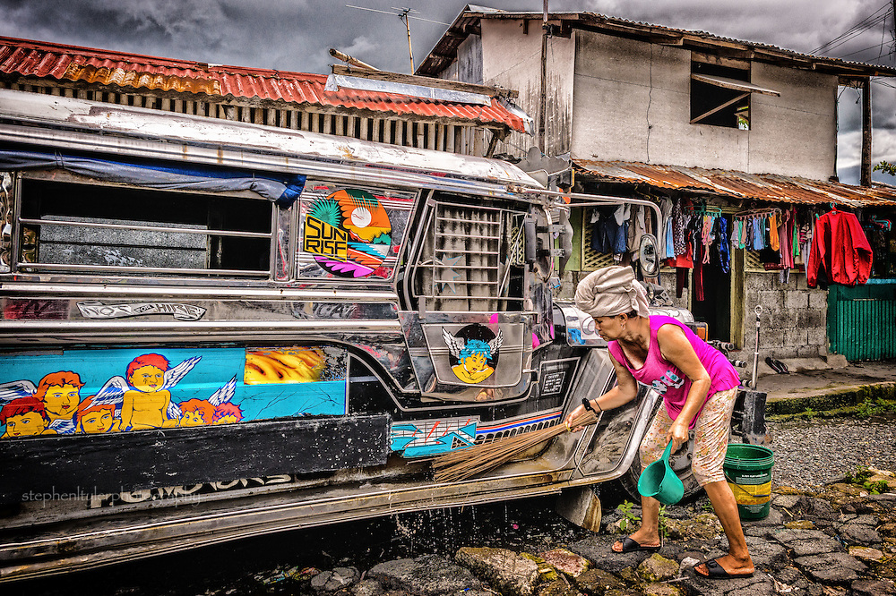 Everyday life in a fishing village community with nearly everything built from bamboo on top of stilts on the edge of a lake. Many residents earn their living away from the village; a woman cleans up a jeepney outside her lakefront home
