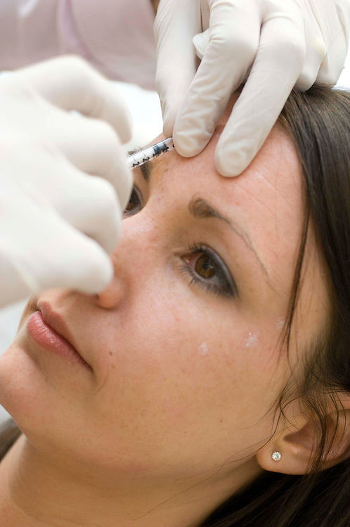 Woman patient receives a Botox injection, England, UK.