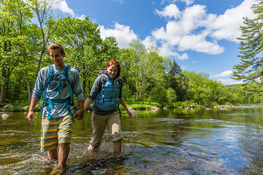 A young couple ford the Pleasant River while hiking on The Appalachian Trail in Maine's 100 Mile Wilderness.