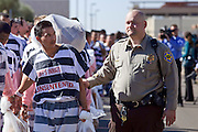 """04 FEBRUARY 2009 -- A county detention officer escorts prisoners to Tent City. Maricopa County Sheriff Joe Arpaio marched about 200 undocumented immigrants in the Durango Jail to """"Tent City"""" where he will house the prisoners until or if they are deported. PHOTO BY JACK KURTZ"""
