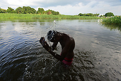June 23, 2017 - Juba, Central Equatorial, South Sudan - A young Muslim man bathes in the Nile River to cope with the heat and the rigor of fasting as the Muslim holy month of Ramadan comes to an end in Juba, South Sudan, the world's newest nation, where civilians have been devastated by a civil war that has left roughly two-thirds of the nation facing famine. (Credit Image: © Miguel Juarez Lugo via ZUMA Wire)