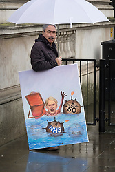 © Licensed to London News Pictures. 07/03/2017. London, UK.Political artist Kaya Mar holds a cartoon of Chancellor of the Exchequer Philip Hammond outside Downing Street as the Spring Budget is delivered to Parliament. Photo credit: Peter Macdiarmid/LNP