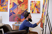 A student, surrounded by his work, paints in his private studio space in the Art buuilding.