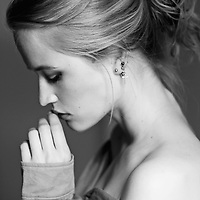 Close black and white portrait of young woman with pensive pose and tied up hair