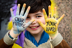 © Licensed to London News Pictures. 15/03/2019. LONDON, UK.  A young student with a message on his hands. Thousands of students take part in a Climate Change strike in Parliament Square, marching down Whitehall to Buckingham Palace.  Similar strikes by students are taking part around the world demanding that governments take action against the effects of climate change.  Photo credit: Stephen Chung/LNP