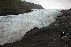 Hikers walk along the edge of Exit Glacier, Kenai Fjords National Park, Alaska, United States of America