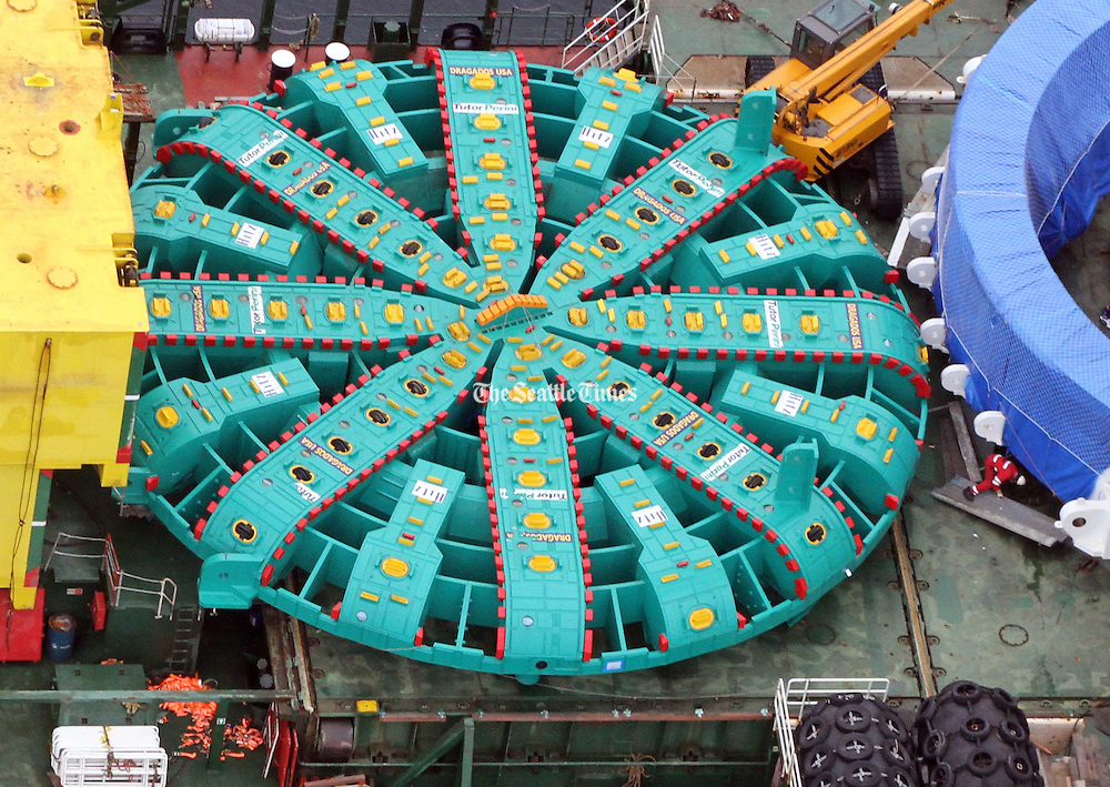 A crew member of the ship carrying Bertha, the giant boring machine, is in red (far right) dwarfed by the 57 1/2-foot cutting face of the machine. <br />