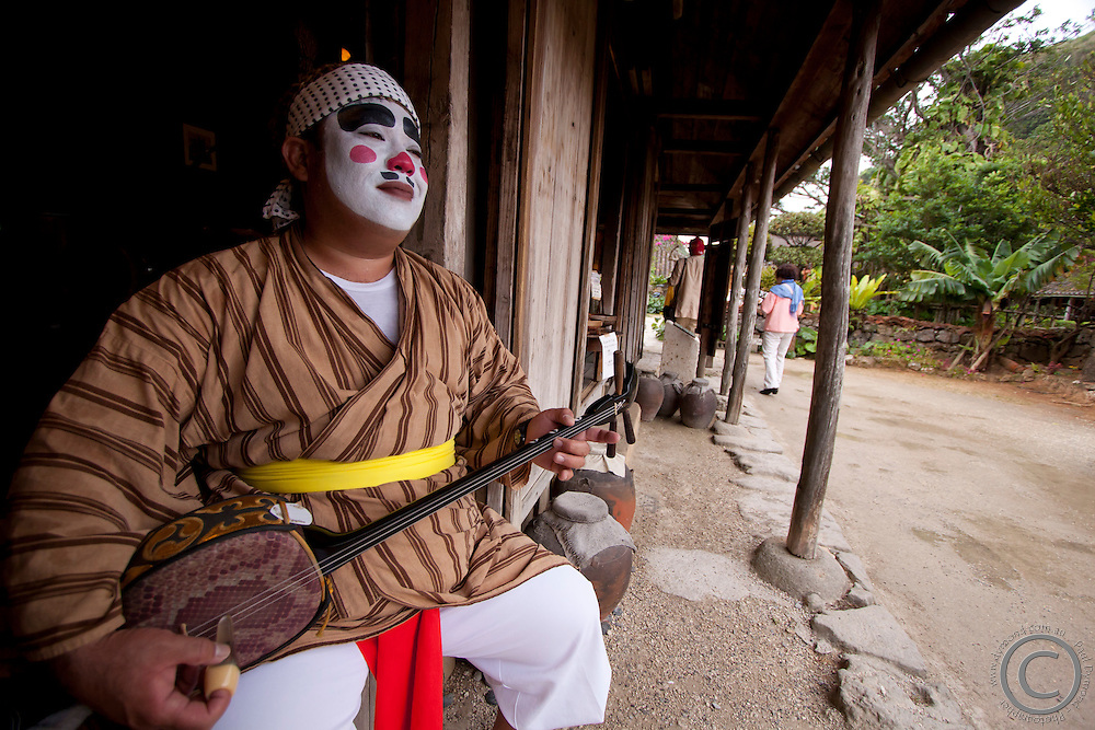 A traditional perfomer in clown costume plays the shamisen for tourists visiting the Ryukyu Mura on the main island of Okinawa.
