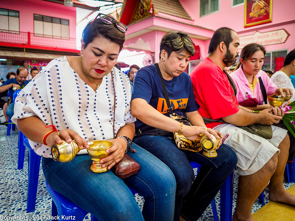 """24 JUNE 2017 - BANG KRUAI, NONTHABURI: People pray before a """"resurrection"""" or rebirthing ceremony at Wat Ta Kien (also spelled Wat Tahkian), a Buddhist temple in the suburbs of Bangkok. People go to the temple to participate in a """"Resurrection Ceremony."""" Thai Buddhists believe that connecting people by strings around their heads, which are connected to a web of strings suspended from the ceiling, amplifies the power of the prayer. Groups of people meet and pray with the temple's Buddhist monks. Then they lie in coffins, the monks pull a pink sheet over them, symbolizing their ritualistic death. The sheet is then pulled back, and people sit up in the coffin, symbolizing their ritualist rebirth. The ceremony is supposed to expunge bad karma and bad luck from a person's life and also get people used to the idea of the inevitability of death. Most times, one person lays in one coffin, but there is family sized coffin that can accommodate up to six people. The temple has been doing the resurrection ceremonies for about nine years.     PHOTO BY JACK KURTZ"""