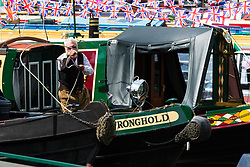 Little Venice, London, April 30th 2017. Narrowboaters from all over the uK gather for the annual Canalway Cavalcade, held on the May Day Bank holiday weekend, organised by the Inland Waterways Association, where boaters get the chance to display their immaculately prepared and brightly painted craft as well as compete in various manoeuvring tests. PICTURED: A man throws a mooring rope from the bow of his narrowboat.<br /> Credit: &copy;Paul Davey<br /> To licence contact: <br /> Mobile: +44 (0) 7966 016 296<br /> Email: paul@pauldaveycreative.co.uk<br /> Twitter: @pauldaveycreate