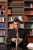 Man wearing suit opening book at desk in library