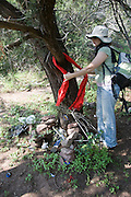 No More Deaths volunteer Heidi Kennedy re-ties a scarf to a tree near a shrine left by migrants that have crossed the Mexico border on their way to Phoenix. The shrine had candles a psalm book and coins.