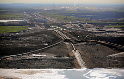CANADA ALBERTA FORT MCMURRAY 23JUL09 - Tailings pipe spews toxic sludge into a pond bordering the Boreal forest at the tarsands mining site of CNRL (Canadian Natural Resources Limited) Horizon site north of Fort McMurray, northern Alberta, Canada...The tar sand deposits lie under 141,000 square kilometres of sparsely populated boreal forest and muskeg and contain about 1.7 trillion barrels of bitumen in-place, comparable in magnitude to the world's total proven reserves of conventional petroleum. Current projections state that production will  grow from 1.2 million barrels per day (190,000 m³/d) in 2008 to 3.3 million barrels per day (520,000 m³/d) in 2020 which would place Canada among the four or five largest oil-producing countries in the world...The industry has brought wealth and an economic boom to the region but also created an environmental disaster downstream from the Athabasca river, polluting the lakes where water and fish are contaminated. The native Indian tribes of the Mikisew, Cree, Dene and other smaller First Nations are seeing their natural habitat destroyed and are largely powerless to stop or slow down the rapid expansion of the oil sands development, Canada's number one economic driver...jre/Photo by Jiri Rezac / GREENPEACE..© Jiri Rezac 2009