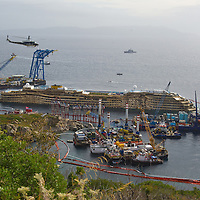 ISOLA DEL GIGLIO, ITALY - SEPTEMBER 17: The severly damaged side of the stricken Costa Concordia is visible after the parbuckling operation succesfully uprighted the ship around 4 am on September 17, 2013 in Isola del Giglio, Italy. Work began yesterday to right the stricken Costa Concordia vessel, which sank on January 12, 2012. If the operation is successful, it will then be towed away and scrapped. The procedure, known as parbuckling, has never been carried out on a vessel as large as Costa Concordia before. (Photo by Marco Secchi/Getty Images)