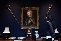 "© Licensed to London News Pictures. 23/03/2017. London, UK.  A staff member views Scottish basket-hilted broadswords, said to be that carried by Alexander, 4th Lord Forbes of Pitsligo (Est. GBP1,200-1,500), which are hanging next to a ""A Portrait of Alexander, 4th Lord Forbes of Pitsligo"" by Alexis-Simon Belle (Est. GBP15-20k).  Preview at Sotheby's New Bond Street of property from two great Scottish families, the Forbeses of Pitsligo and the Marquesses of Lothian, which will be auctioned in London on 28 March.   Photo credit : Stephen Chung/LNP"
