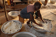 A woman prepares meal from the kasaba plant, Korantang, Ghana
