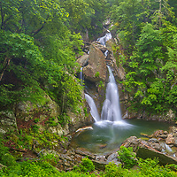 Visiting Bash Bish Falls State Park is always a ton of fun. Bash Bish Falls is one of the most scenic and beautiful waterfalls in New England. So glad to have the falls relatively near by in Berkshires County of Massachusetts, 2 hours and 30 minutes from home to be precise. It's been a while since I came out here photographing waterfalls but last Friday time was right and I traveled to Western Massachusetts to visit my favorite waterfall in the Bay State. Upon arrival, rain was still coming down in a good pace. I grabbed an umbrella and walked the 3/4 mile from the parking area to the falls. The adrenaline level rose with each step I took alongside Bash Bish Brook, the roaring of the falls became apparent and louder as closer I got. Then you arrive at your final destination, looking straight ahead, facing these majestic falls. It's just amazing and I love this scenic waterfall view. Equipped with my Canon 24-70mm lens I got to work capturing this  highest single drop waterfall. Rain and keeping the lens dry was a pain at first, but luckily it stopped raining soon after I started photographing. This made things more pleasant and easier, allowing for further exploration of this Waterfall Photography hotspot and more picture taking.<br />