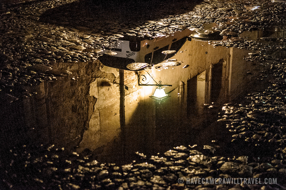 A puddle in the cobblestone street of Antigua, Guatemala, reflects the street lights and the yellow colonial building.