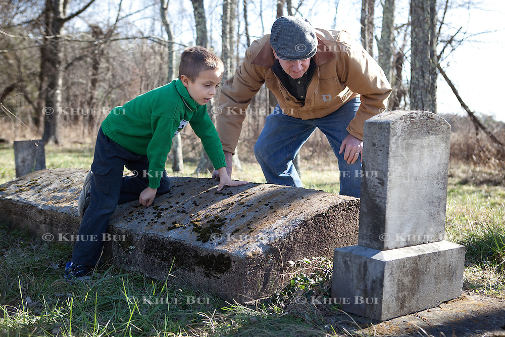 John W. Sanderson (age 75, brown coat); and Clinton Sanderson Sancho (age 6, green sweatshirt), grandson of John W. Sanderson; visit the private family cemetery Thursday, December 22, 2016, in Cartersville, VA.  The private cemetery contains 4 named graves, but the family believes there are more family members buried here as there are more stones next to the named grave sites.<br /> <br /> Photo by Khue Bui for the New York Times