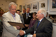 Mike Grimes, Chairman of the Seaford Photographic Society presenting Glyn Bareham with Lifetime Membership the Society.<br /> <br /> Seaford Photographic Exhibition 2012 in The Crypt, Seaford, East Sussex 25 August - 09 September