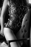 Artistic black and white closeup of a sexy woman body in black lacy underwear bodysuit with leather bondage straps tied on top