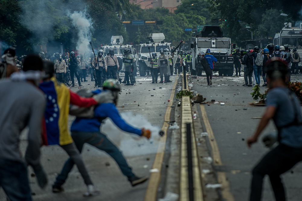 CARACAS, VENEZUELA - MAY 20, 2017:  Anti-government protesters throw rocks and molotov cocktails at members of the National Police, who responded by heavily tear gassing and firing rubber bullets and buckshot at them.  The streets of Caracas and other cities across Venezuela have been filled with tens of thousands of demonstrators for nearly 100 days of massive protests, held since April 1st. Protesters are enraged at the government for becoming an increasingly repressive, authoritarian regime that has delayed elections, used armed government loyalist to threaten dissidents, called for the Constitution to be re-written to favor them, jailed and tortured protesters and members of the political opposition, and whose corruption and failed economic policy has caused the current economic crisis that has led to widespread food and medicine shortages across the country.  Independent local media report nearly 100 people have been killed during protests and protest-related riots and looting.  The government currently only officially reports 75 deaths.  Over 2,000 people have been injured, and over 3,000 protesters have been detained by authorities.  PHOTO: Meridith Kohut