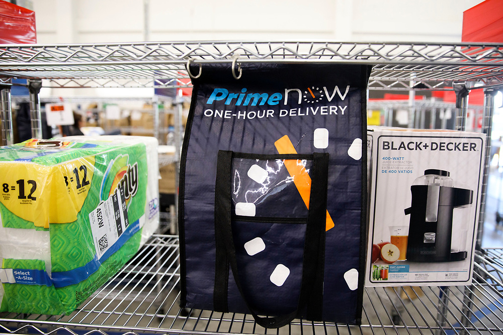 A bag containing Amazon Prime Now one-hour delivery cold items awaits delivery on a shelf next to a case of paper towels and a juice extractor at the Amazon.com Inc. Prime Now fulfillment center warehouse on Monday, March 27, 2017 in Los Angeles, Calif. The warehouse can fulfill one and two hour delivery to customers. Complex supply chains such as Amazon's and e-commerce trends will impact city infrastructure and how things move through cities. © 2017 Patrick T. Fallon