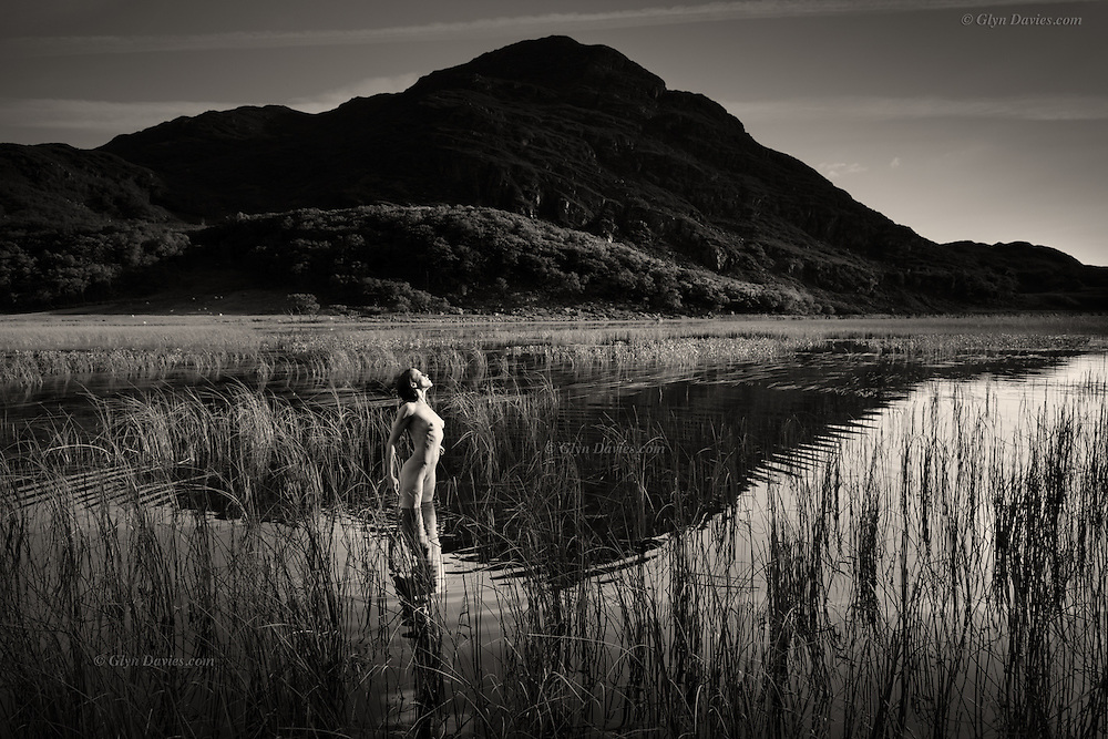 In this lonely valley nestles a large but often calm lake. Reeds puncture the glassy smooth surface and there is silence, apart from the occasional bleating of Welsh mountain sheep, or the call of a raven over the hillsides. This woman is so bird-like in stature, so graceful and so slim, that she reminds me of the heron which frequents this place. She delicately points each foot into the lake so as not to overly disturb its surface and even in the act of doing this mimics the beautiful creature. She turns to face the light, her front feeling the gentle warmth of the afternoon sun, as the cold water clasps her legs. She stands motionless, embracing these sensations as I watch her.