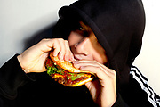 A young hooded boy eating a fast food burger.