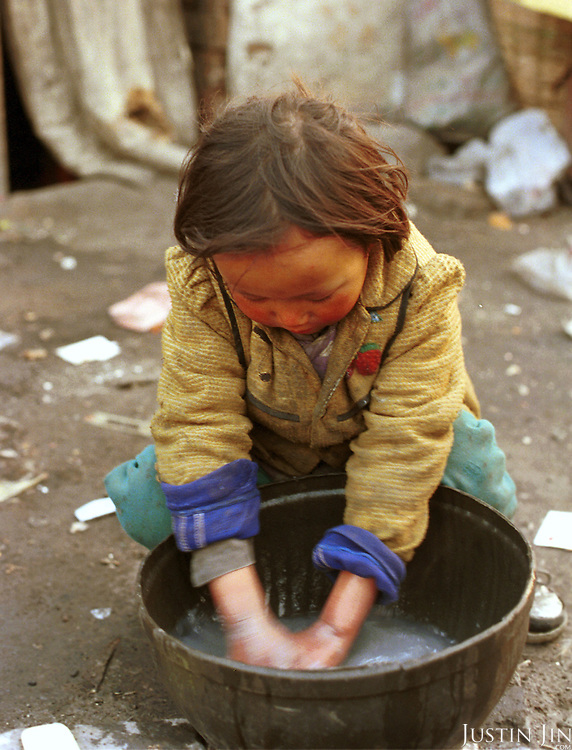 Wei's daughter washes her hands after playing among the trash at the garbage dump in Beijing...Children at the garbage dump are not entitled to schooling in the Chinese capital, which faces big problems with the constant influx of rural migrants. Experts estimate that about 40 million rural workers roam Chinese cities looking for jobs, bringing with them a further 30 million spouses and children...Picture taken March 1999.Copyright Justin Jin
