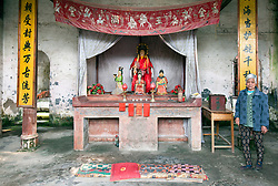 Interior, Buddhist Temple, Yangshuo Hutong, Southern China. The Chinese lady would not let anyone leave until they had contributed yuan to the temple's upkeep.