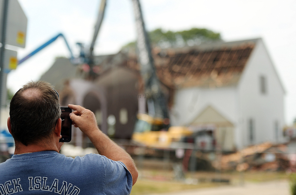 7/25/16 :: REGION :: STAND ALONE :: Jimmy Brennan, of Pawcatuck, snaps a photo as workers from Stamford Wrecking tear-down St. Michael The Archangel Roman Catholic Church on Liberty St. in Pawcatuck Monday, July 25, 2016. Brennan's parents were married in the church 65-years ago and he and his five bothers were all baptized there. Brennan came out Friday to watch the demolition begin and came back Monday to see if he could see them remove the altar. The church has been closed since April of 2012 when structural problems were found. The new church will be built on the original foundation. (Sean D. Elliot/The Day)
