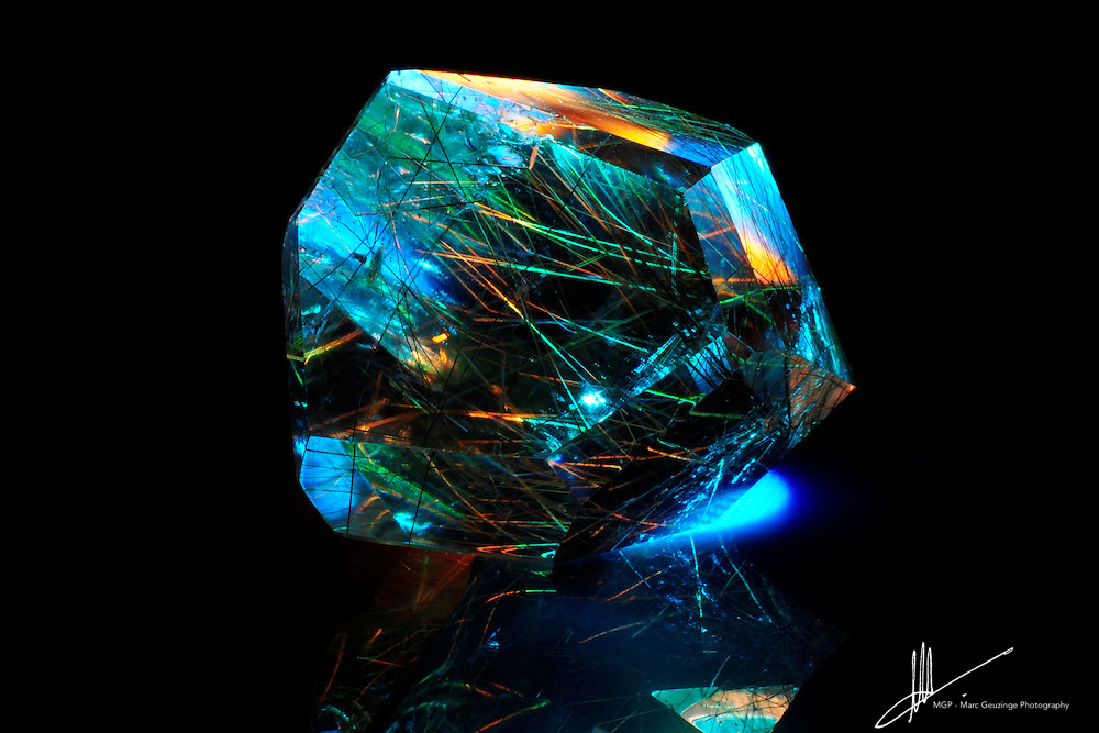 This Rutilated Quartz piece shows of its strands of rutile, bathed in a blue and green light with fiery accents.