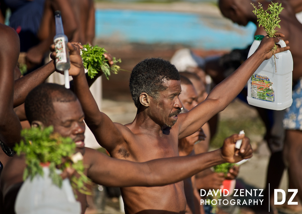 Pilgrims raise their arms holding basil, candles and liquor while facing the sea during a sunrise voodou ritual at Bord de Mer de Limonade, on the north coast of Haiti on July 25, 2008. After renewing their faith in the mud pit at Plaine du Nord on the days prior, pilgrims migrate to the nearby water, their faith renewed.