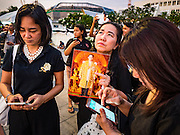05 NOVEMBER 2016 - BANGKOK, THAILAND:  A woman with a photo of Bhumibol Adulyadej, the late King of Thailand, watches the sun set behind the Grand Palace in Bangkok while her friends text on their smart phones. Crowd of mourners continue to go to the palace to honor the King, nearly three weeks after his death. Thais are honoring their late King, Bhumibol Adulyadej, also known as Rama IX, in various ways. Many barbers are offering mourners free haircuts on the streets near the Grand Palace, where the King is lying in state and communities around the palace are offering free meals to mourners walking to the palace.    PHOTO BY JACK KURTZ