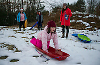 Andy Hession shows families to the sledding hill as Prescott Farm Environmental Center celebrates the Winter Solstice on Saturday.  (Karen Bobotas/for the Laconia Daily Sun)