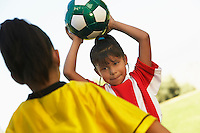 Girl soccer player (7-9 years) preparing to throw ball