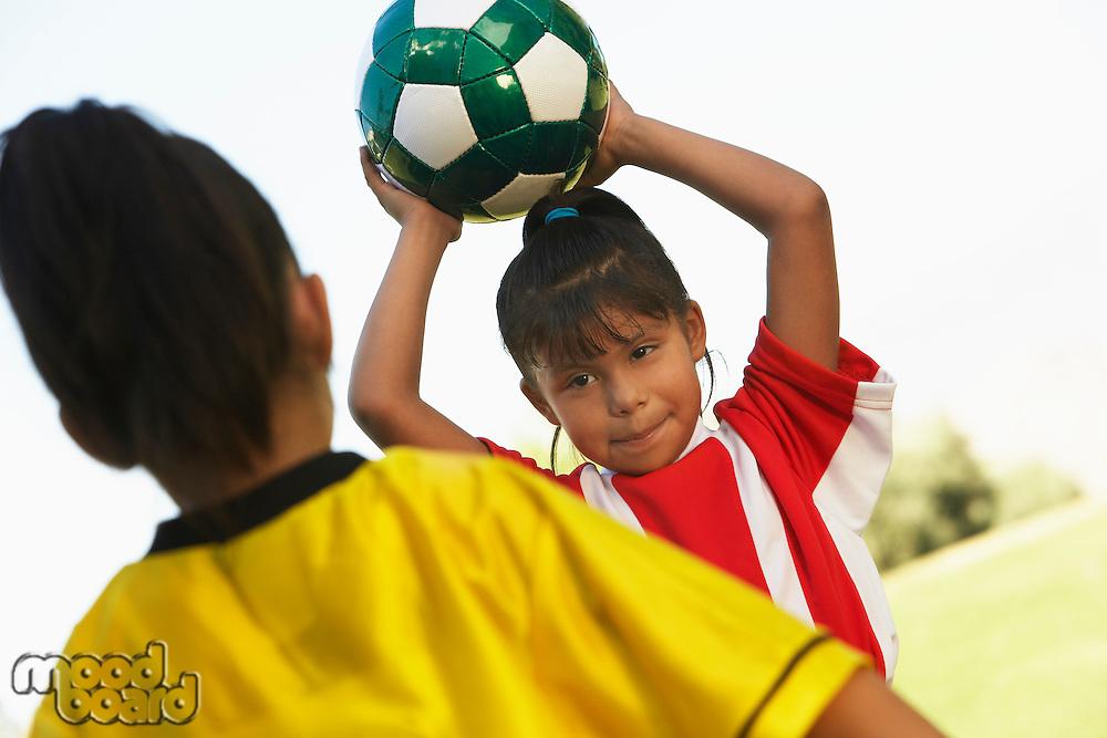 Girl soccer player (7-9 years) preparing to throw ball