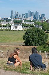 ©Licensed to London News Pictures 22/07/2020     <br /> Greenwich, UK. Two people sitting on the grass in Greenwich park, London with a view of Canary Wharf while chatting. Warm hot sunny weather in the UK today.  Photo credit: Grant Falvey/LNP