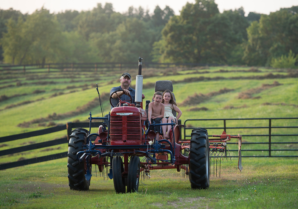 A farmer and his children ride in their tractor on Skyline Farm in Grass Lake, Mich. August 5, 2014.