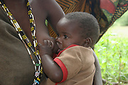 Africa, Tanzania, Lake Eyasi, Portrait of a young Hadza mother breast feeding her baby, A small tribe of hunter gatherers AKA Hadzabe Tribe April 2006