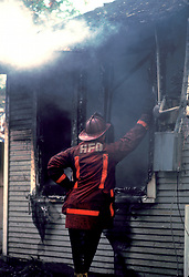 Stock photo of a Houston fire fighter examining the inside of a burned house through the window