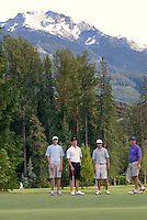 Foursome lines up in front of Whistler mountain, on Nicklaus North Golf course, Whistler, BC Canada.