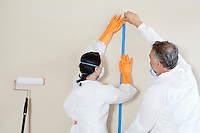 Back view of two manual workers doing preparation to paint room