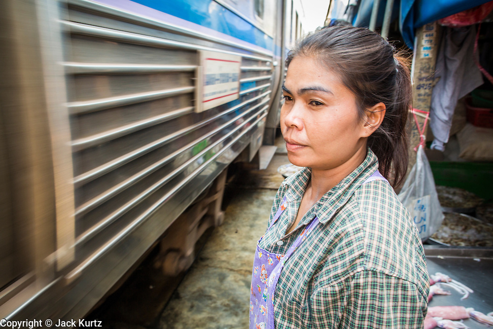 17 JANUARY 2013 - SAMUT SONGKHRAM, SAMUT SONGKHRAM, THAILAND: A vendor watches a train pass through the market in Samut Songkhram. Four trains each day make the round trip from Baan Laem, near Samut Sakhon, to Samut Songkhram, the train chugs through market eight times a day (coming and going). Each time market vendors pick up their merchandise and clear the track for the train, only to set up again when the train passes. The market on the train tracks has become a tourist attraction in this part of Thailand and many tourists stop to see the train on their way to or from the floating market in Damnoen Saduak.    PHOTO BY JACK KURTZ